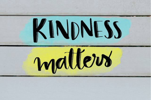 Kindness matters hand lettering inspirational message on grey wooden background