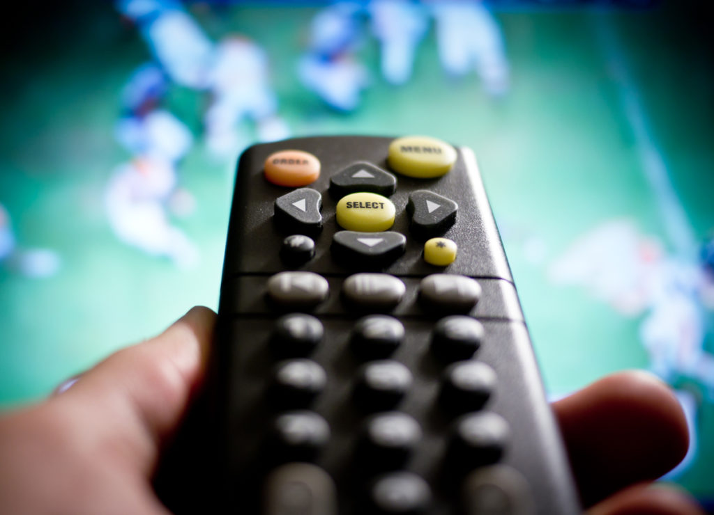 A man with a remote watching football on his tv